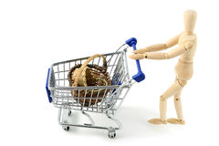 Wooden mannequin shopping with a cart on white backgrou royalty free stock photos