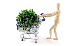 Wooden mannequin shopping with a cart on white backgrou stock photo
