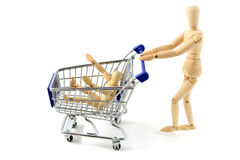 Wooden mannequin shopping with a cart on white backgrou stock image