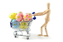 Wooden mannequin shopping easter eggs in shopping cart on white. Background royalty free stock photos