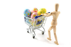 Wooden mannequin shopping easter eggs in shopping cart on white Stock Images
