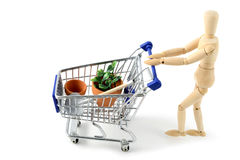 Wooden mannequin shopping garden items. Wooden mannequin going shopping with shopping cart of garden plants and tools royalty free stock photo