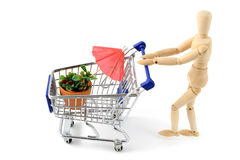 Wooden mannequin shopping garden items. Wooden mannequin going shopping with shopping cart of garden plants and tools royalty free stock images