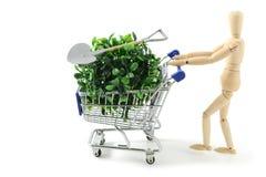 Wooden mannequin shopping garden utensils in a shopping cart at stock image
