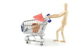 Wooden mannequin shopping garden utensils in a shopping cart at stock photography
