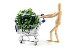 Wooden mannequin shopping garden utensils in a shopping cart at royalty free stock image