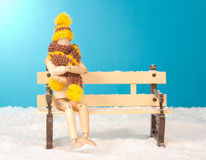 Wooden mannequin sitting on a bench. Wooden mannequin wearing a scarf and hat sitting on a bench cold in the snow royalty free stock photo