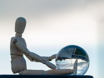 Wooden mannequin sitting with a crystal ball in his hands reflecting a landscape Ecology concept. Wooden mannequin sitting with a crystal ball in his hands Royalty Free Stock Photos