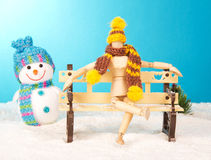 Wooden mannequin on a snowy bench. Wooden mannequin sitting on a bench next to a snowy snowman royalty free stock photos