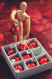 Wooden mannequin sorting christmas balls Royalty Free Stock Images