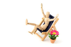 Wooden mannequin sunbathing in a chair.  royalty free stock photos