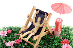 Wooden mannequin sunbathing in a chair.  stock images