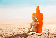 Wooden mannequin and sunscreen at beach. Wooden mannequin and sunscreen at the beach stock images