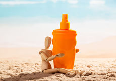 Wooden mannequin with sunscreen on seashore. Wooden mannequin with sunscreen on the seashore stock images