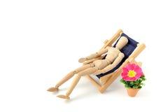 Wooden mannequin taking sunbath in deck chair. On background stock photos