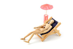 Wooden mannequin taking sunbath in deck chair. On background stock photography