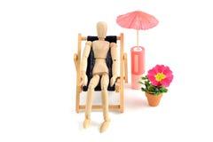 Wooden mannequin taking sunbath in deck chair Stock Image