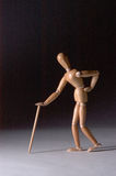 Wooden Mannequin Walking With Cane. A wooden modelling mannequin walking with a cane on a black graduated background Stock Photo