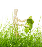 Wooden mannequin with watering can in grass isolated on white. Wooden mannequin with a watering can in the grass isolated on white background stock photography