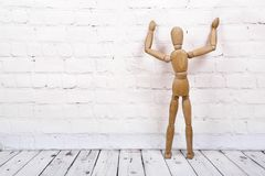 Wooden mannequin on white brick background stock photos