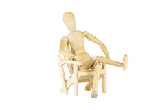 Wooden mannequin on a wooden chair royalty free stock photography