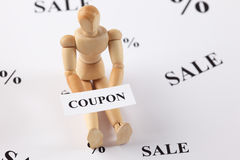 Wooden mannequin with word Coupon. A wooden mannequin holds a word Coupon. White background with wold sale and percent Stock Photo