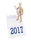 Wooden mannequin writing - 2017. Wooden mannequin writing in a scrapbook - 2017 stock photo