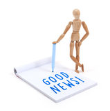 Wooden mannequin writing in scrapbook - Good news Royalty Free Stock Photography