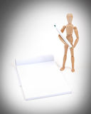 Wooden mannequin writing. In a scrapbook, isolated royalty free stock photos
