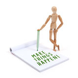 Wooden mannequin writing in scrapbook - Make things happen royalty free stock image