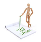 Wooden mannequin writing in scrapbook - Never stop learning stock photo
