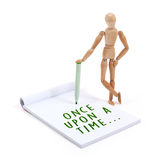 Wooden mannequin writing in scrapbook - Once upon a time. Wooden mannequin writing in a scrapbook - Once upon a time stock photo