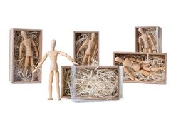 Wooden mannikin is standing near open cardboard box filled with wood shred while others are remaining inside. Concept of thinking outside the box, freedom royalty free stock photos