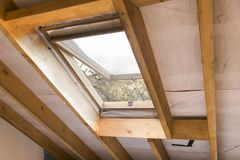 Wooden mansard or skylight window on attic. Attic renovation and. Insulation Stock Photography