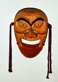 Wooden mask. Grinning wooden mask from Thailand, with painted eyebrows and pendant strings Stock Images