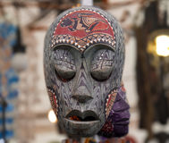 Wooden mask. Painted wooden mask with a second mask in the background Royalty Free Stock Photography