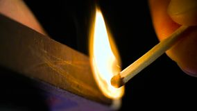 A wooden match breaks out with fire and burns on a black background shot using a high-speed camera sony FS700. HD stock footage