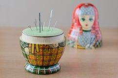 Wooden matryoshka doll-pincushion. Sewing needle royalty free stock photo