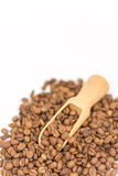 Wooden measuring spoon in pile of raw coffee Stock Images