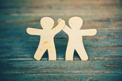 Wooden men holding hands. Wooden little men holding hands on wooden boards background. Symbol of friendship, love and teamwork Stock Photography