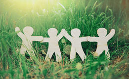 Wooden men holding hands. Wooden little men holding hands in summer grass. Symbol of friendship, family, teamwork or ecology concept Stock Images