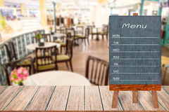 Wooden menu display sign, Frame restaurant message board on wooden table, Blurred image background. Stock Image