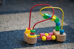 Wooden and metal toy for toddlers with small geometric objects on wires. Used for development of small motor skills in kids royalty free stock photography