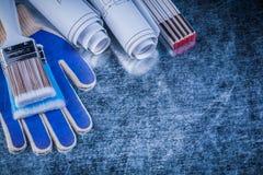 Wooden meter paint brush safety gloves blueprints on metallic ba Stock Photography