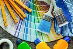 Wooden meter protective gloves paint brush bottles color palette. On wooden board stock photography