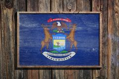 Wooden Michigan flag. 3d rendering of a Michigan State USA flag on a wooden frame and a wood wall Stock Photos