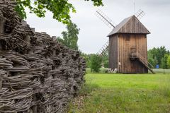 Wooden mill and braided fence in the countryside Royalty Free Stock Photo