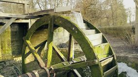 Wooden miller wheel with water turn. Historic medieval village architecture. Static day stabilized shot stock footage
