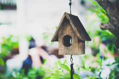 Wooden miniature bird house on green tree - vintage tone stock photo