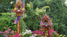 Wooden miniature guardian spirit house. Small buddhist temple shrine, colorful flower garlands. San phra phum erected to. Bring fortune. Traditional respect stock footage